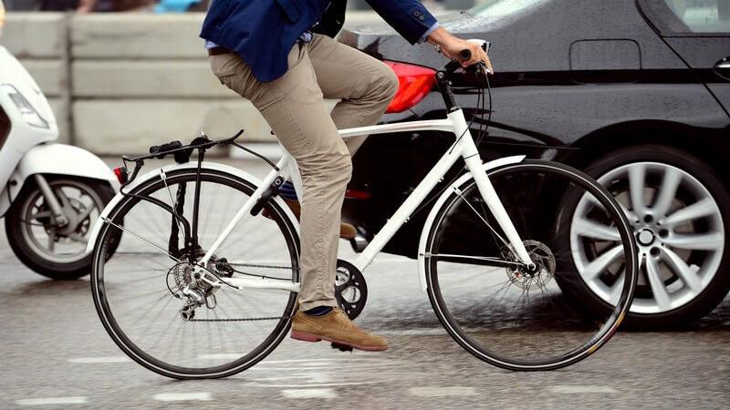 Mann in grauer Hose und braunen Lederschuhen auf einem weißen Fahrrad im Stadtverkehr