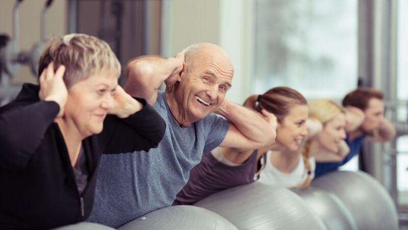 Alte und junge Menschen beim Fitnesstraining mit grauen Gymnastikbällen