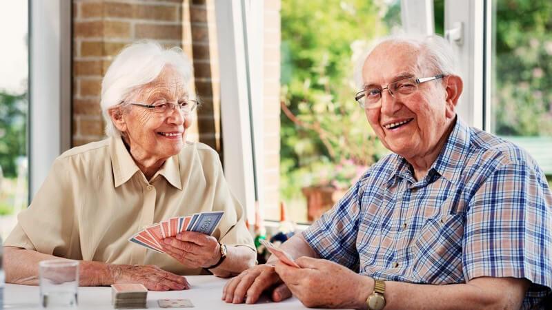 Altes Ehepaar sitzt lächelnd am Tisch und spielt Karten