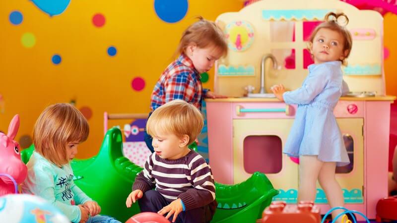 Vier Kleinkinder beim Spielen in einer bunten Kindergartengruppe, überall liegt Spielzeug wie Bälle und eine Spielküche