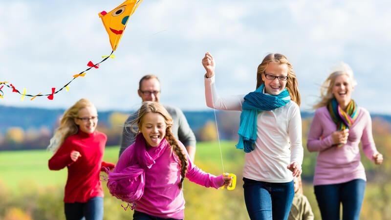 Drei Mädchen rennen mit ihren Eltern und lassen einen Drachen steigen