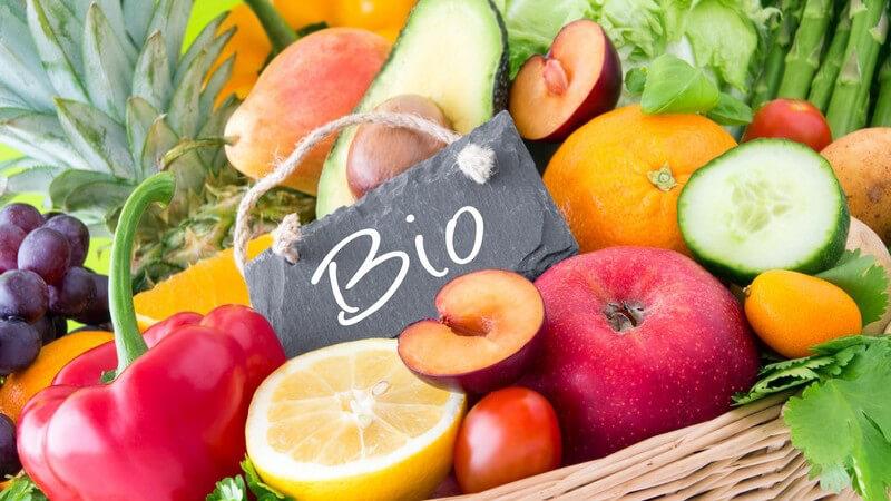 """Frisches Obst und Gemüse im Weidenkorb, mittendrin ein Schild mit der Aufschrift """"Bio"""""""