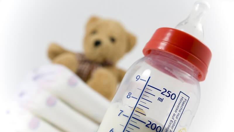 Babyflasche mit Milch, dahinter Windeln und Teddy