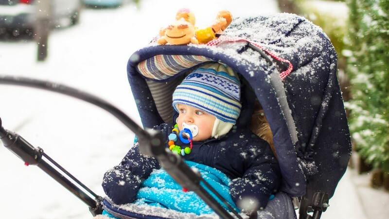 Baby mit Schnuller, dick eingepackt in einem Kinderwagen im Schnee
