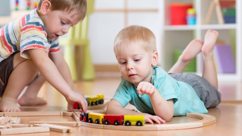 Zwei kleine Jungen spielen im Kinderzimmer mit einer Holzeisenbahn