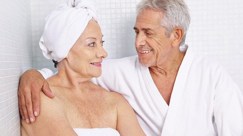 Seniorenpaar sitzt im weiß gefliesten Spa, bekleidet mit weißem Handtuch bzw. Bademantel