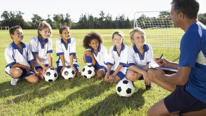Jugendfußballmannschaft bei einer Besprechung mit ihrem Trainer auf dem Rasen