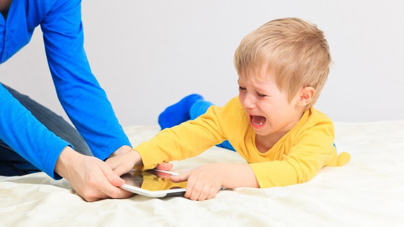 Mutter versucht ihrem kleinen Sohn im gelben Shirt einen Tablet-Computer zu entreißen