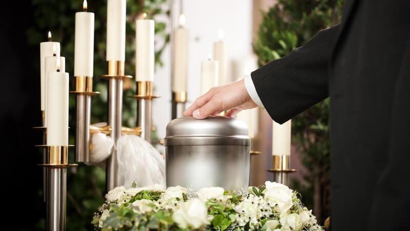 Beerdigung: Hand eines Mannes im schwarzen Anzug auf Urne, im Hintergrund weiße Kerzen