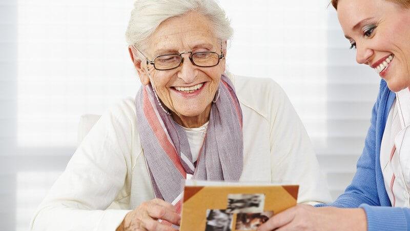 Lächelnde Seniorin sieht sich mit ihrer Tochter ein altes Fotoalbum an