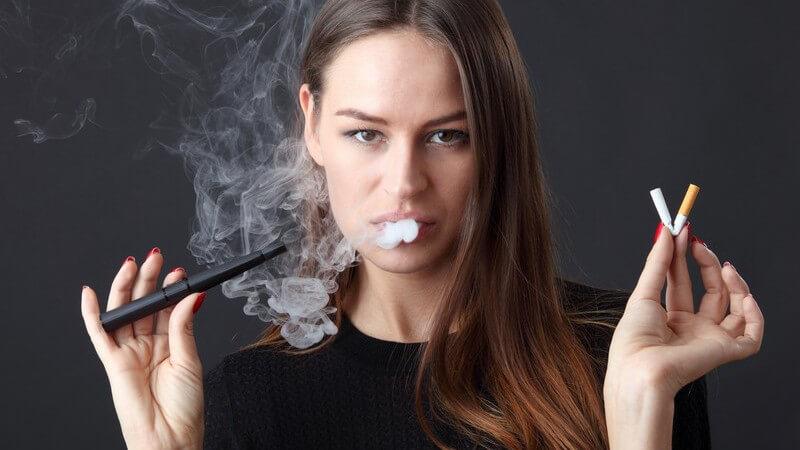 Dunkelhaarige Frau vor schwarzem Hintergrund dampft eine E-Zigarette und hält eine geknickte Filterzigarette in der Hand