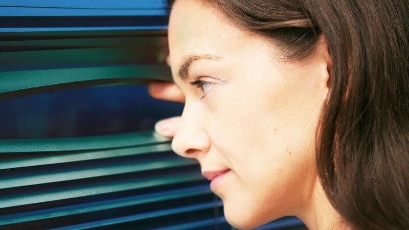 Junge Frau schaut durch Jalousien aus dem Fenster