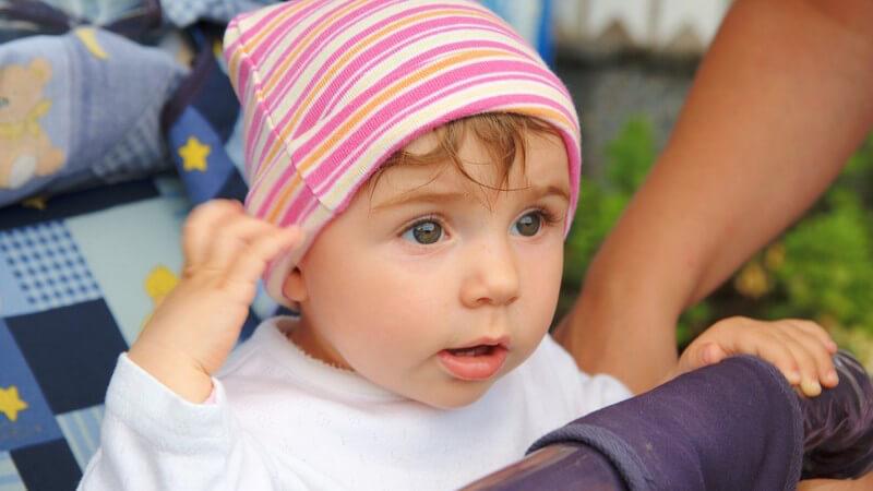 Baby mit rosa Mütze im Kinderwagen
