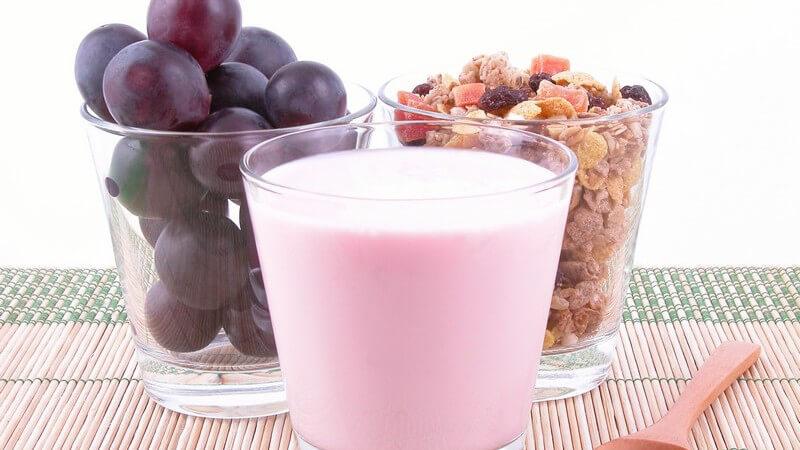 Drei Gläser mit Joghurt, Trauben, Müsli auf Tisch