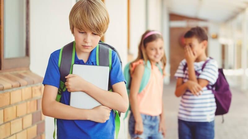 Schüler in blauem Poloshirt und mit grünem Rucksack hält ein Tablet und wird im Hintergrund von zwei Schülern verspottet