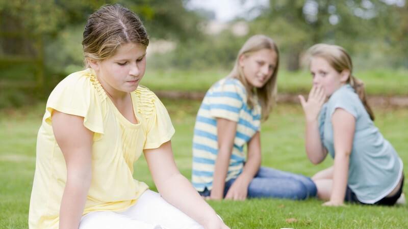 Mädchen sitzt traurig auf Wiese und wird von Mädchen im Hintergrund ausgelacht