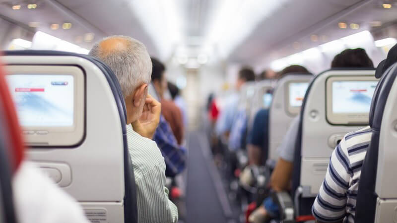 Blick durch den langen Gang eines vollbesetzten Passagierflugzeugs