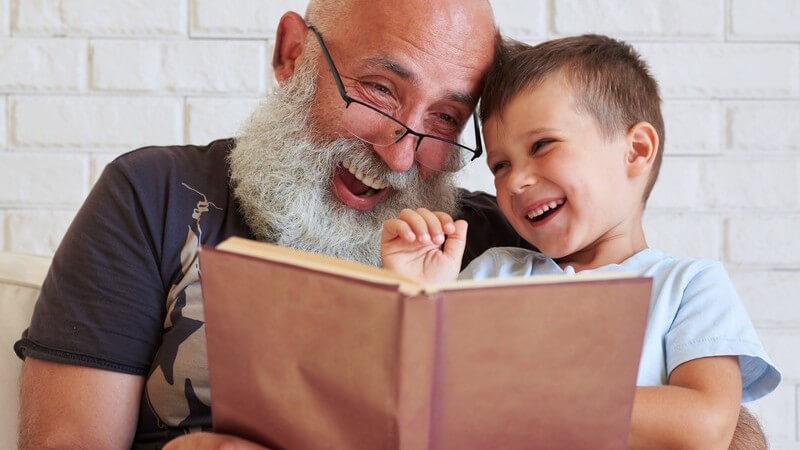 Großvater mit langem Bart und Brille liest seinem Enkelsohn ein Buch vor, beide lachen