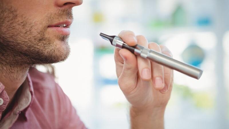 Mann mit Dreitagebart hält eine silberne E-Zigarette