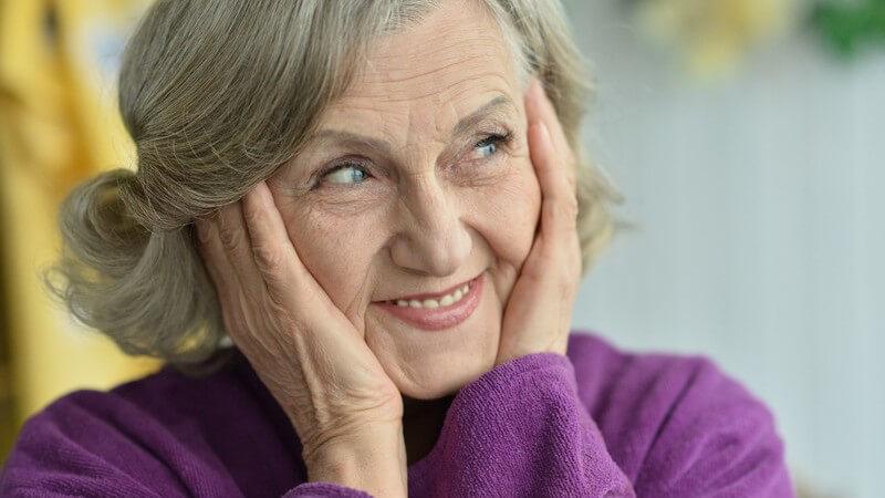 Alte Frau in lila Kleidung hält die Hände ans Gesicht und lächelt verschmitzt zur Seite