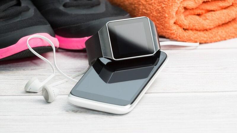 Smartphone, Smartwatch und Kopfhörer neben pinken Laufschuhen und Handtuch