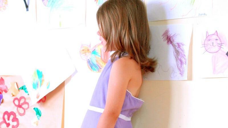Kleines Mädchen in lila Kleid lehnt an Wand mit gemalten Kinderbildern