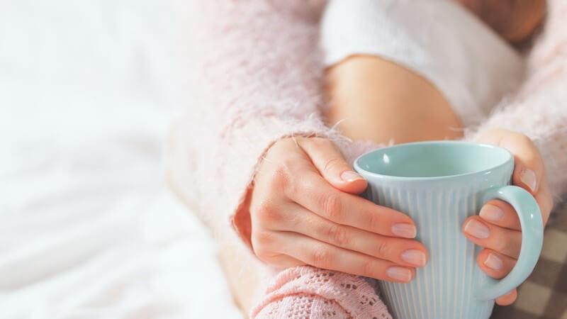Junge Frau in rosa Socken und Wollpulli sitzt auf dem Bett und relaxt mit türkiser Tasse in den Händen