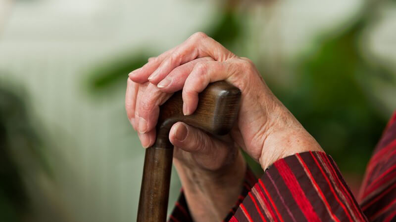 Nahaufnahme Hände alter Frau auf Gehstock gestützt