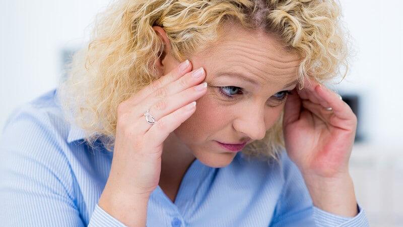 Frau mit Dauerwelle und blauer Bluse sitzt mit Kopfschmerzen im Büro und fasst sich an die Schläfen