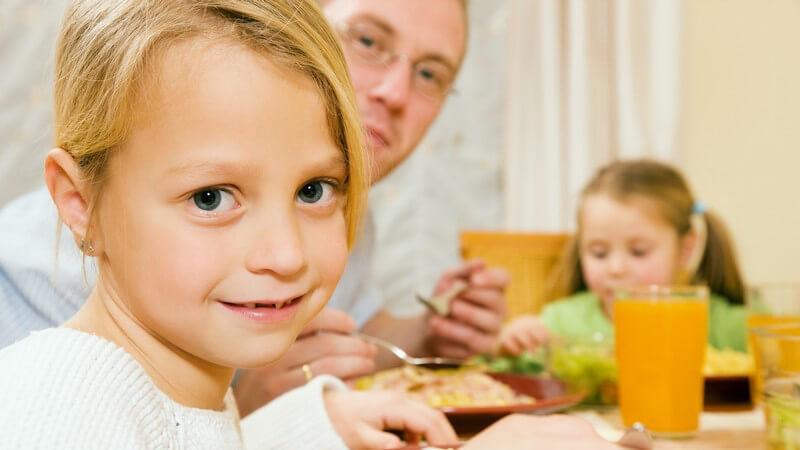 Familie am Tisch beim Essen, kleine Tochter lächelt schüchter in Kamera