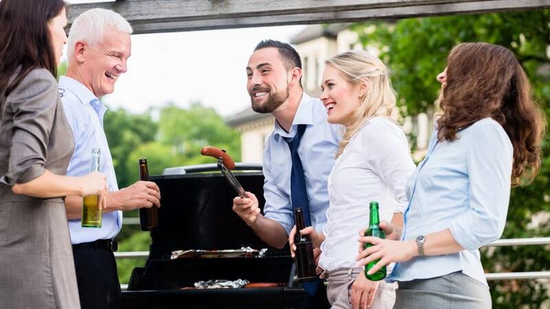 Arbeitskollegen und -kolleginnen grillen Würstchen und trinken ein Bierchen nach Feierabend
