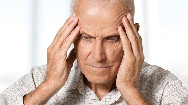 Älterer Mann in beigem karierten Hemd hält die Hände an seine Schläfen