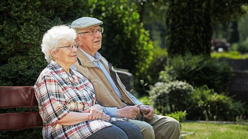 Senioren, älteres Paar sitzt auf Parkbank oder auf dem Friedhof