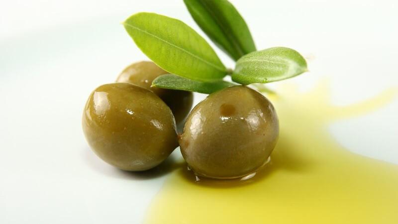 Drei grüne Oliven mit Blättern liegen im gelben Olivenöl