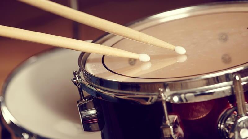 Zwei Drumsticks schlagen auf eine Trommel