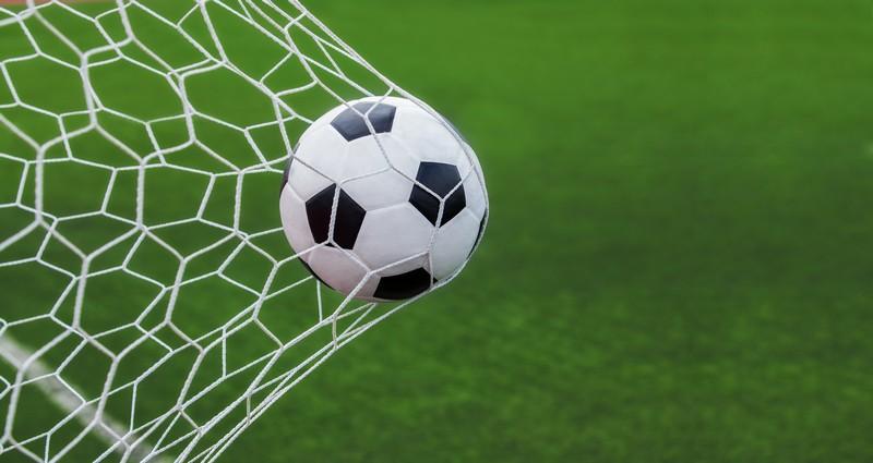 Ins Tornetz fliegender Fußball auf Rasenplatz