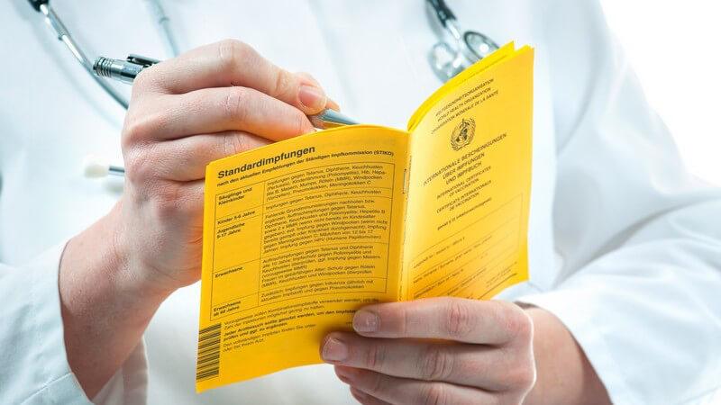 Arzt trägt etwas in einen gelben Impfausweis ein