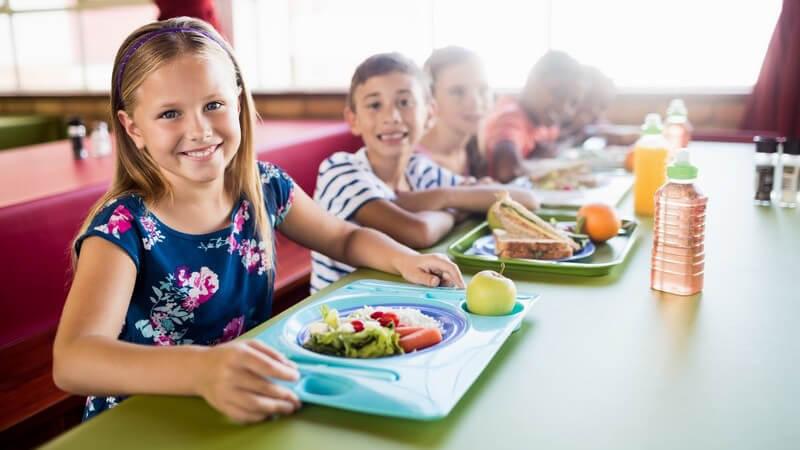 Mädchen in blauem Sommerkleid und andere Kinder sitzen mit ihrem Essen an einem großen grünen Tisch in der Schulkantine