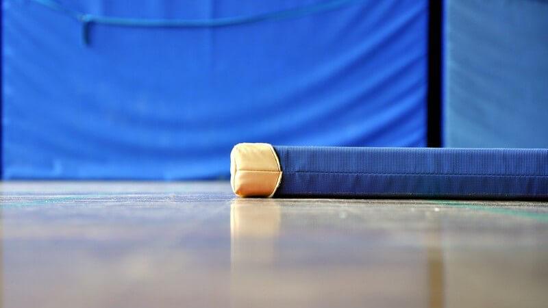 Blaue Turnmatte mit brauner Lederecke liegt auf dem Boden einer Turnhalle, im Hintergrund stehen große Sprungmatten