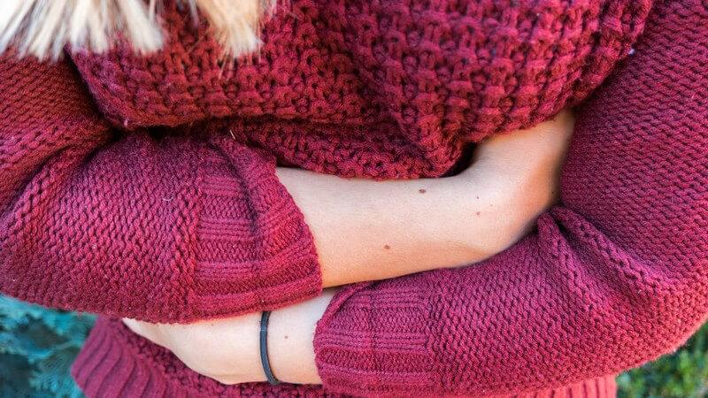 Über dem Bauch verschränkte Arme einer blonden Frau in rotem Wollpullover mit Bauchschmerzen