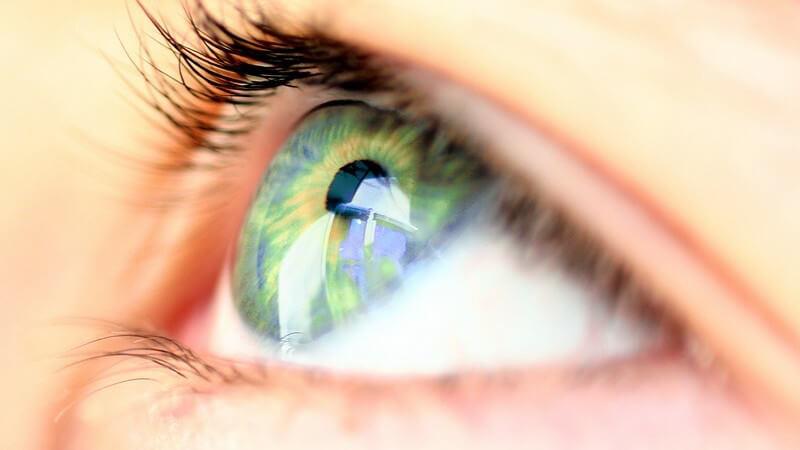 Nahaufnahme grünes Auge einer jungen Frau, Blick nach oben, Foto von Seite