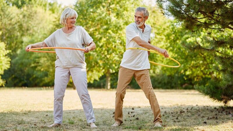 Mann und Frau beim Seniorensport in einem Park, machen Übungen mit einem Hula-Hoop-Reifen