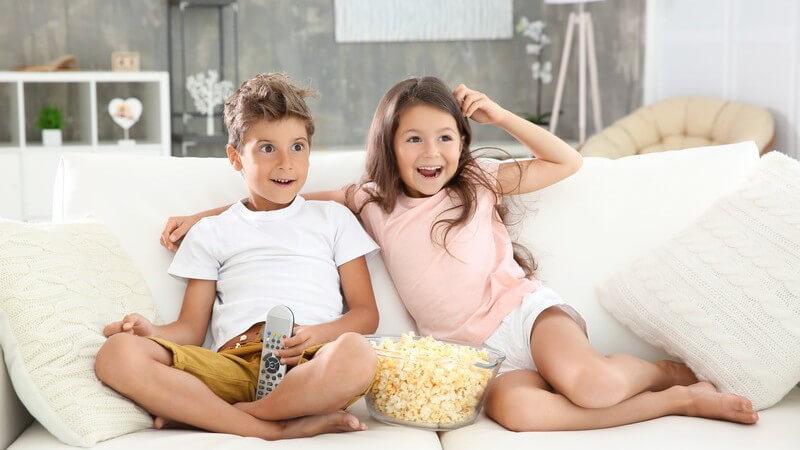 Bruder und Schwester sitzen gemütlich mit einer großen Schüssel Popcorn auf der weißen Couch und gucken Fernsehen