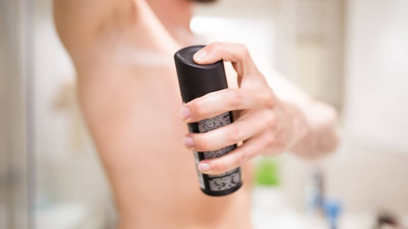 Mann steht im Badezimmer und sprüht sich Deodorant unter die rechte Achsel, schwarzes Deospray