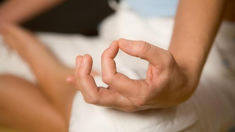 Nahaufnahme auf Knie aufgestützte Hand, Yogaübung