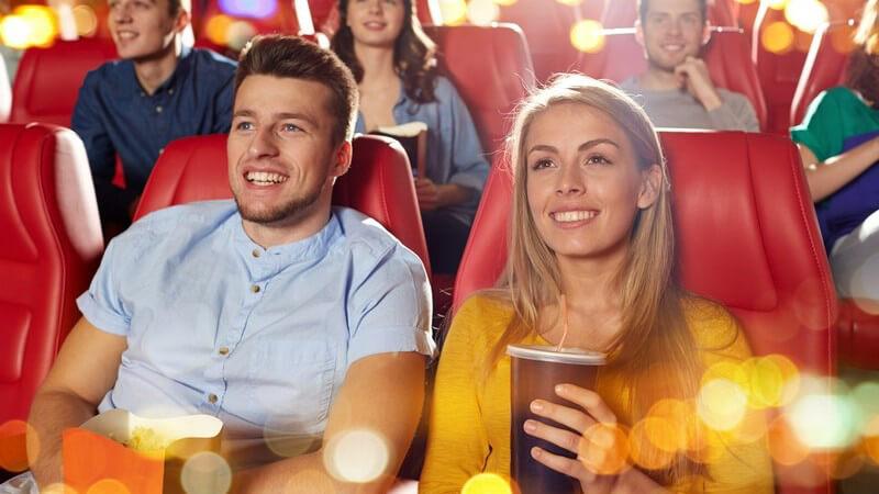 Junge Kinozuschauer mit Popcorn und Getränken in roten Sitzen