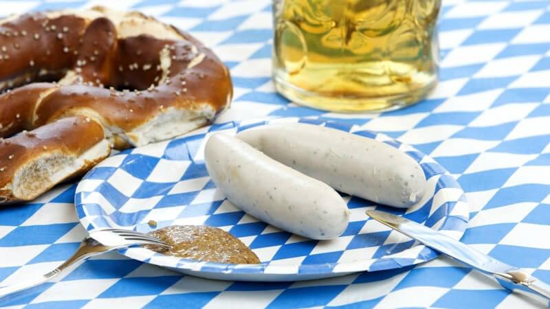 Weisswürste mit Senf, Brezel, Weissbier auf blau-weißer Tischdecke