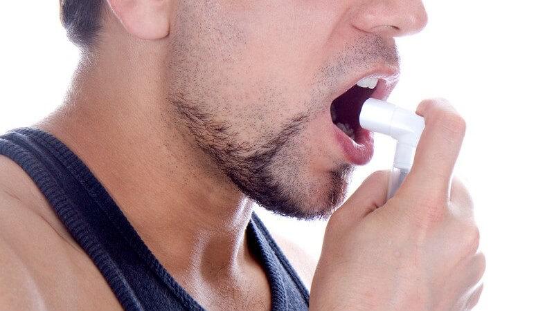 Nahaufnahme Mann hält Beatmungsgerät vor Mund, Asthma