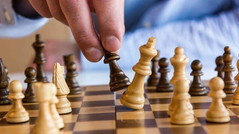 Mann schlägt den weißen König beim Schachspiel