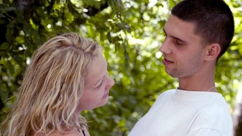 Blonde Frau und Mann mit sehr kurzen Haaren und weißem T-Shirt schauen sich im Wald intensiv an